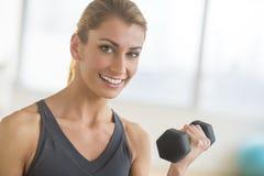 Mulher feliz que levanta peso no health club Foto de Stock