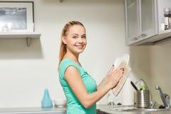 Mulher feliz que limpa a cozinha dos pratos em casa imagem de stock