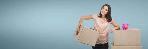 Mulher feliz que mantém caixas com o mealheiro contra o fundo azul foto de stock