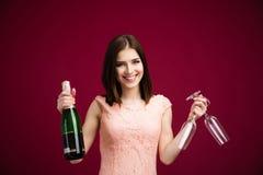 Mulher feliz que mantém dois de vidro e a garrafa do champanhe Fotos de Stock