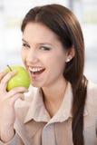 Mulher feliz que morde um sorriso da maçã Imagens de Stock Royalty Free