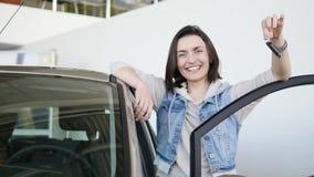 Mulher feliz que mostra a chave de seu carro novo Auto negócio, venda do carro, tecnologia e conceito dos povos - homem feliz com filme