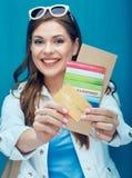 Mulher feliz que mostra o pasport, o cartão de crédito e o bilhete para o feriado fotos de stock