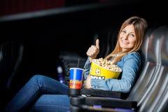 Mulher feliz que mostra Thumbsup no teatro do cinema Imagem de Stock