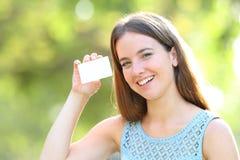 Mulher feliz que mostra um cartão de crédito vazio em um parque fotografia de stock royalty free