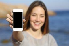 Mulher feliz que mostra uma exposição esperta do telefone na praia Fotos de Stock Royalty Free