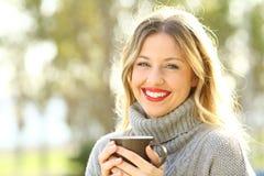 Mulher feliz que olha a câmera com uma xícara de café Fotografia de Stock