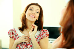 Mulher feliz que olha em sua reflexão no espelho Fotos de Stock
