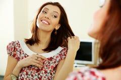 Mulher feliz que olha em sua reflexão no espelho Imagens de Stock