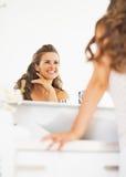 Mulher feliz que olha no espelho no banheiro fotografia de stock