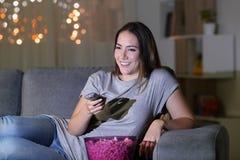 Mulher feliz que olha o índice da tevê na noite em casa fotografia de stock royalty free