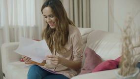 Mulher feliz que olha papéis de negócio em casa Mulher de neg?cio que faz o documento video estoque