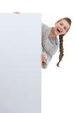 Mulher feliz que olha para fora do quadro de avisos em branco Fotografia de Stock