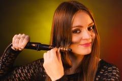 Mulher feliz que ondula seu cabelo marrom longo foto de stock