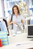 Mulher feliz que paga na loja da roupa Fotos de Stock