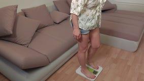 Mulher feliz que pisa na escala de peso vídeos de arquivo