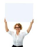 Mulher feliz que prende o quadro de avisos em branco foto de stock