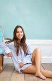 Mulher feliz que relaxa em casa e que inclina-se na cadeira Fotografia de Stock Royalty Free