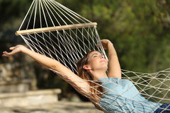 Mulher feliz que relaxa em uma rede em feriados e que aumenta os braços Fotos de Stock Royalty Free