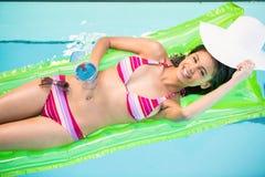 Mulher feliz que relaxa na cama de ar na piscina Foto de Stock