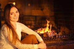 Mulher feliz que relaxa na chaminé Casa do inverno Fotografia de Stock