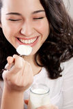 Mulher feliz que ri com os olhos fechados ao comer um yogurt Foto de Stock Royalty Free