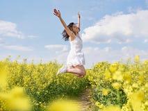 Mulher feliz que salta com as mãos levantadas exteriores fotografia de stock royalty free