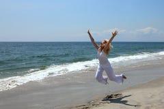 Mulher feliz que salta em uma praia Fotografia de Stock Royalty Free