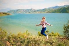 Mulher feliz que salta fora a natureza Dia de verão bonito imagem de stock royalty free