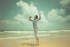 Mulher feliz que salta na praia fotografia de stock