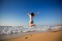 Mulher feliz que salta na praia Imagens de Stock