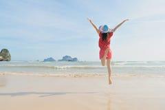 Mulher feliz que salta na praia em Krabi Tailândia fotografia de stock