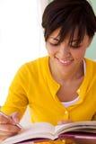 Mulher feliz que senta-se dentro da escrita em um jornal Fotos de Stock