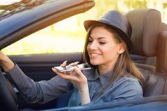Mulher feliz que senta-se dentro do carro convertível usando uma função esperta do reconhecimento de voz do telefone na linha fotografia de stock royalty free