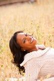 Mulher feliz que senta-se em um sorriso do campo Foto de Stock