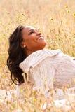 Mulher feliz que senta-se em um sorriso do campo Imagem de Stock