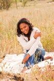 Mulher feliz que senta-se em um sorriso do campo Imagens de Stock Royalty Free