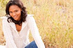 Mulher feliz que senta-se em um sorriso do campo Imagens de Stock