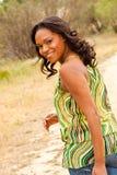 Mulher feliz que senta-se em um sorriso do campo Fotos de Stock Royalty Free