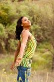 Mulher feliz que senta-se em um sorriso do campo Imagem de Stock Royalty Free