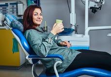 Mulher feliz que senta-se em uma cadeira do dentista que guarda um copo com colutório em uma clínica foto de stock
