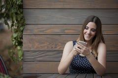 Mulher feliz que senta-se na cafetaria de madeira imagem de stock royalty free