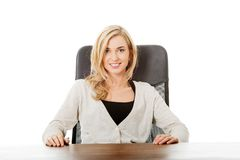 Mulher feliz que senta-se na mesa Imagem de Stock Royalty Free