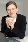 Mulher feliz que senta-se na poltrona com computador portátil, guardarando a caneca de café, olhando a câmera Fotos de Stock