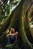 Mulher feliz que senta-se na sombra de uma árvore Fotografia de Stock Royalty Free