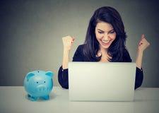 A mulher feliz que senta-se na tabela que olha o portátil comemora a boa notícia imagens de stock