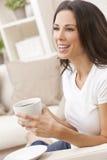 Mulher feliz que senta-se no chá ou no café bebendo do sofá Fotografia de Stock Royalty Free
