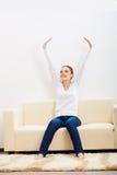 Mulher feliz que senta-se no sofá foto de stock royalty free