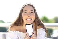 Mulher feliz que sorri mostrando a tela do smartphone imagens de stock