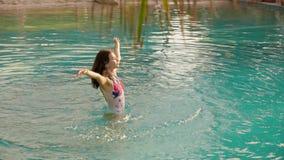 Mulher feliz que tem o divertimento na piscina do hotel video estoque